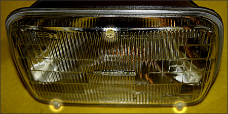 What is the primary reason there are three bumps (also known as pads or nibs) on the lens of a sealed beam headlight?